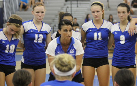 Varsity volleyball players Taylor Matushek (12), Maddie Hirschfield (9), Megan Malestetinic (11), and Brooke Renner (10) listen to Coach Tina Tinberg as she encourages the team during a timeout. The team lost their game to Crown Point on Tuesday, August 28 in the Lake Central gymnasium.