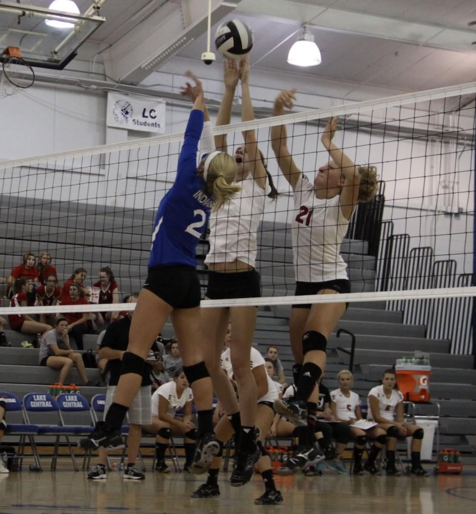 Nikki Garza (12) leaps up to spike the ball over the net during the home Volleyball match against Portage on Thursday, August 30. The ball flew over the net and scored a point for LC.