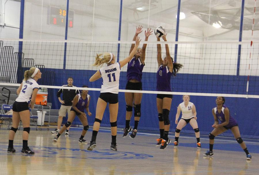 Nichole Garza (12) and  Megan Malatestinic (11) defend the LC Varsity's side of the net at a home Volleyball game against Merrillville. Malatestinic stopped the ball and prevented Merrillville from scoring a point.