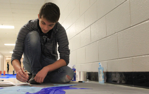 "Jacob Graziani (10) paints a shark on a banner to hang on the hallway wall. The Sophomores went with a ""Jaws"" theme as a twist on the Homecoming theme ""Under the Sea."""