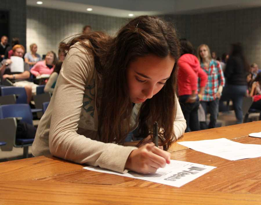 Caroline Haddad (9) signs the N-Teens attendance sheet. The club meets on Thursdays in the LGI room or in E200.