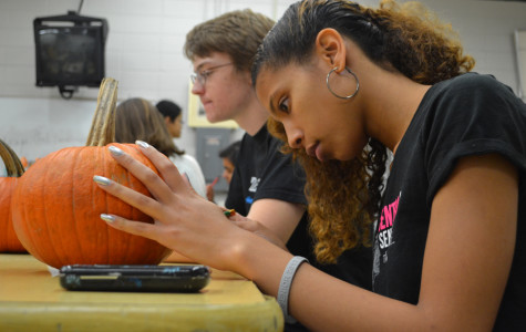 Branae' Collier (12) paints her pumpkin at the Art Club Halloween party.  Collier decorated her pumpkin with Bubbles, the Powerpuff Girl character.