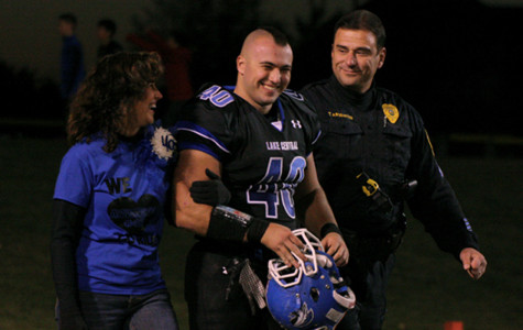 Riley Arvanitis (12) and his parents walk across the football field together Friday night. After years of long practices, senior night was a night of recognition for all of the students and their families who gave up so much of their time for their sport.