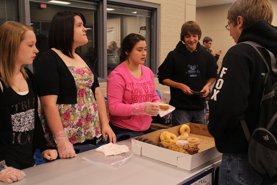 Members of Dollars for Scholars sell a donut to Nicholas Brooker (12). The money they raised goes towards their scholarships.