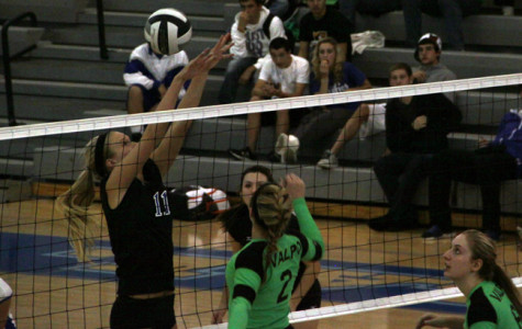 Megan Malantestinic (11) attempts to block a spike hit by a Valpo opponent. Taylor Ellis (10) and Julianne Epperson (12) covered Malantestinic and scored a point for LC.
