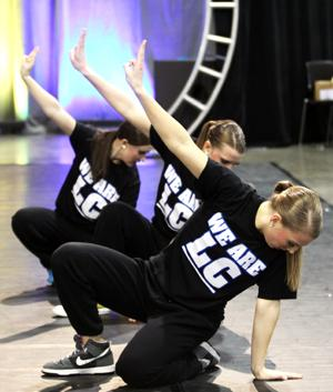 Michelle Gentz (11), Tari Markowski (11), and Amanda Roberts (10) put up the symbol that represents District 12 in the movie The Hunger Games.  The girls finished their Hunger Games-based Hip-Hop dance strong.
