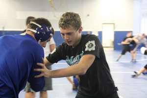 Bryan Tunis (9) practices live wrestling during wrestling practice after school. The team practices together in the upper room over the gymnasium after they run in the hallways.