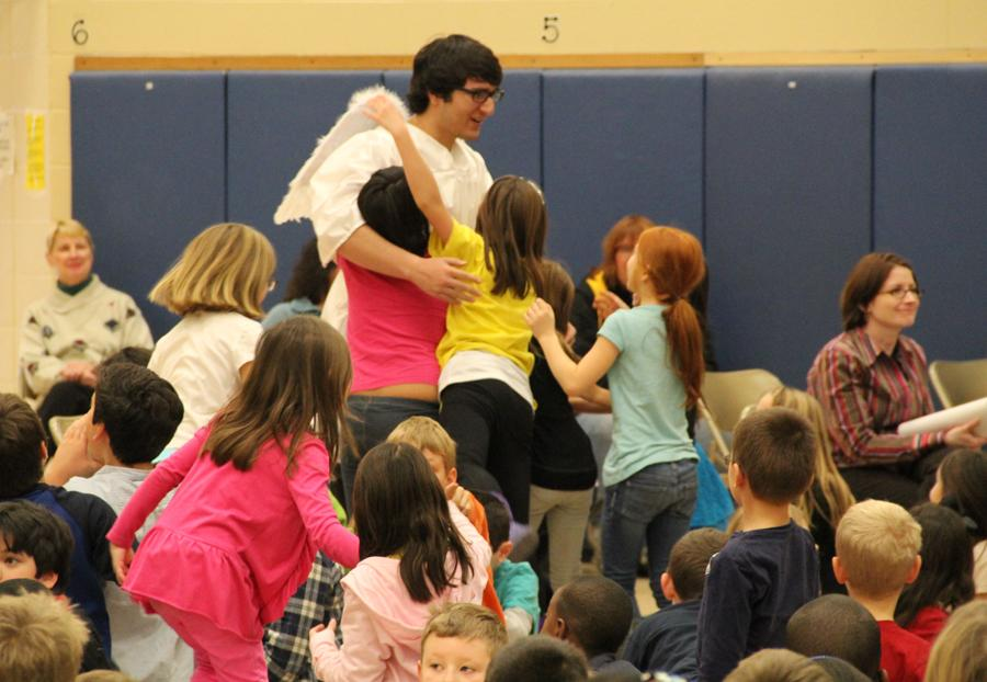 Jacob Quintanilla (12) hugs students of Bibich Elementary dressed as the Monotone Angel. The bells and choirs went to Bibich and Peifer Elementary Schools to perform a holiday concert.