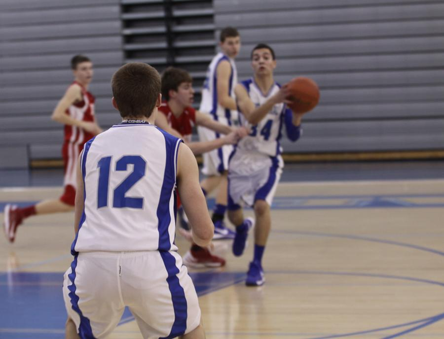 Ryan Bereda (9) stretches up to block Crown Point's shot. Despite their efforts, the A team suffered a four-point loss.