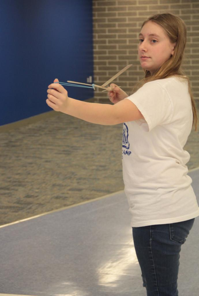 Sarah Dingman (11) launches her elastic launch glider outside of the cafeteria.  The Science Olympiad members had to use the cafeteria so the launchers would not get stuck in the ceiling.