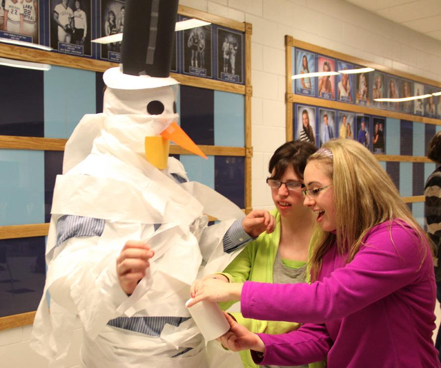 Krysta Rietveld (10) and Taylor Barchi (10) wrap toilet paper around Chase Lowden (10) in order to decorate him as a snowman during a Best Buddies meeting. The club took part in different activities at the meetings.