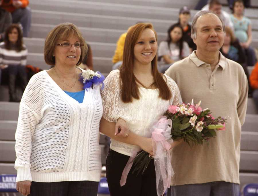 Jaclyn+Schymanski+%2812%29+smiles+at+the+crowd++with+her+parents+Deborah+and+John+Schymanski+when+announced+on+senior+night.The+three+senior+gymnasts+were+acknowledged+before+the+varsity+boys+basketball+game+against+LaPorte.