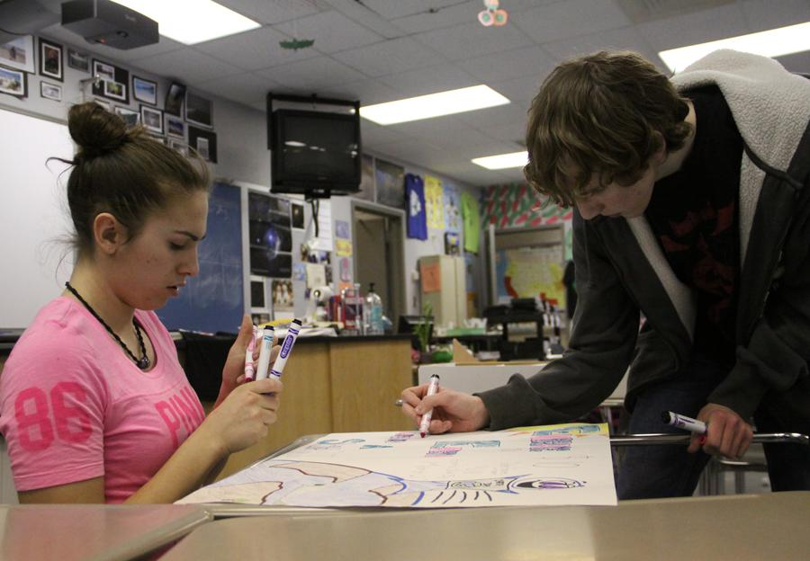 Brianna Dougherty (10) and Brandon Kozel (11) color posters to advertise the new Earth Day T-shirts they will be selling in the near future.  The club started four years ago and has been active ever since.