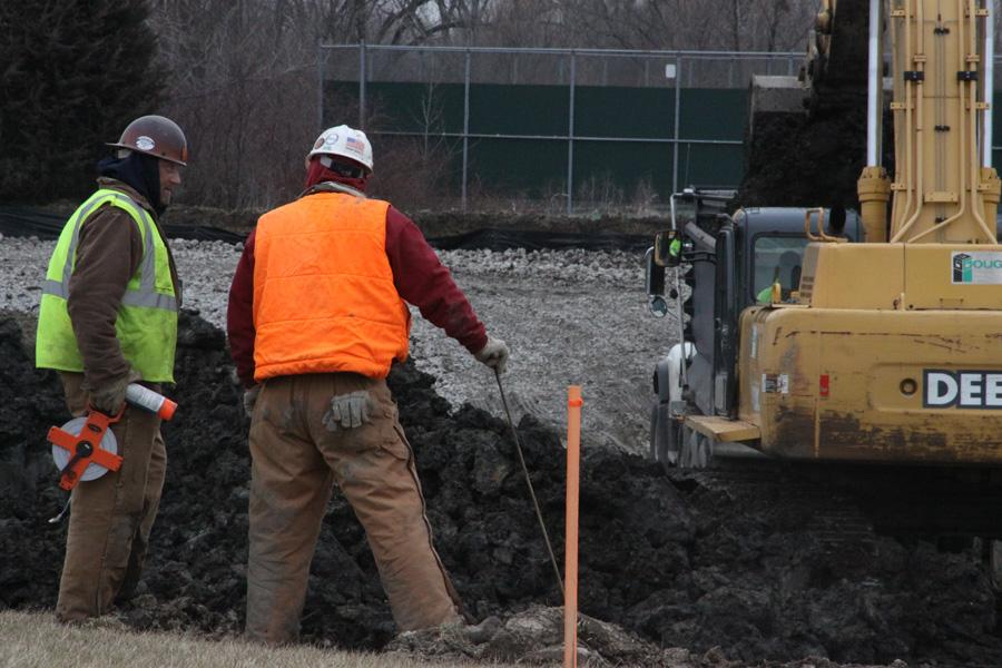 Construction workers talk briefly while working on the beginning stages of creating a drainage basin.  The area will eventually become a field that can be used by the community.