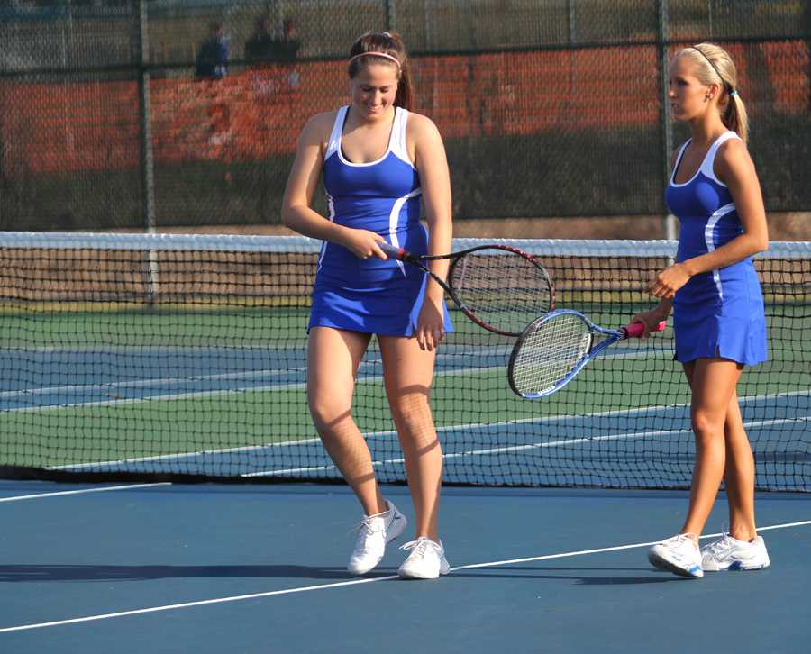 Vanessa Olson (12) and Nicole Stanek (12) hit their rackets together in celebration of winning their match.  Olson and Stanek competed as Varsity 1 doubles.