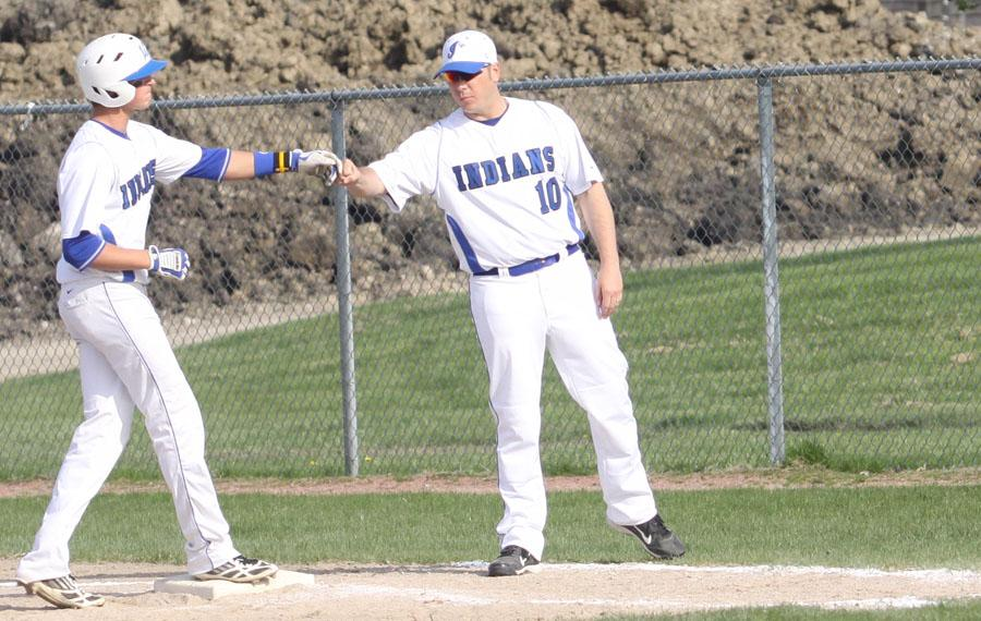 Coach Joe Stanisz fist-bumps Alec Olund (11) after Olund's single. Olund went 2-for-3 with a walk in a 7-3 Crown Point victory on Monday, April 29.