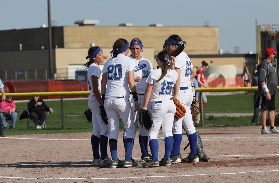 The varsity girls softball team gathers at the pitcher's mound. The girls were determining a plan of action to defeat Portage.