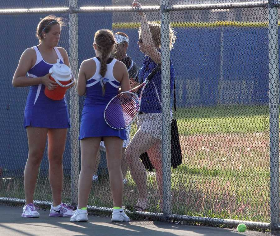 Vanessa Olson (12) and Marlo Owczarak (12) discuss their strategy with Coach Katelin Muesing. The girls went on to win their match at Highland High School against Lowell in straight sets.