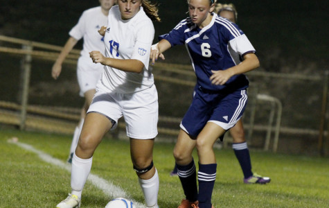 Ashley Halterman (12) faces off with a Michigan City opponent for the ball. The play led to one of the many shots taken on the Wolves that night.