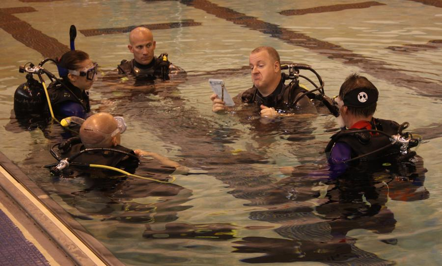Chris Gordon, Dive Control Specialist, reads members of the scuba diving class instructions. The group then puts on the masks and snorkels and goes under water.
