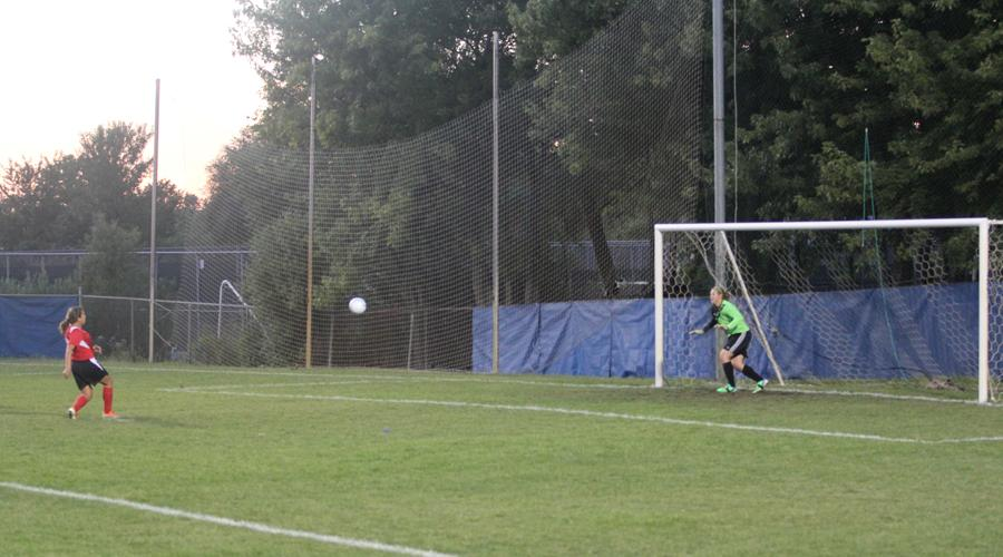 Lindsay Kusbel (11) attempts to stop a goal shot from the opposing team.  The ball was deflected off her hand preventing the team from scoring.