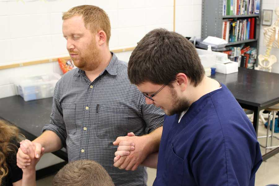 Dr. Dustin Verpooten, Science, and Chase Lowden (11) hold hands while praying in a group prayer. At the end of all Word of Life meetings, the members come together and say a final prayer to end their meeting.