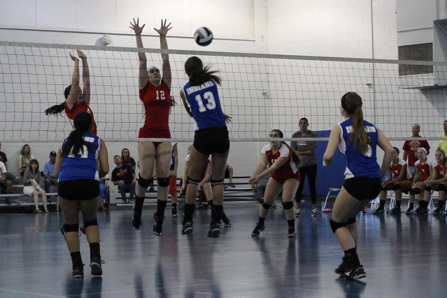Anna Mihajilovic (9) hits the ball over the net while her opponent attempts to block her hit. Mihajilovic successfully spiked the ball and scored.