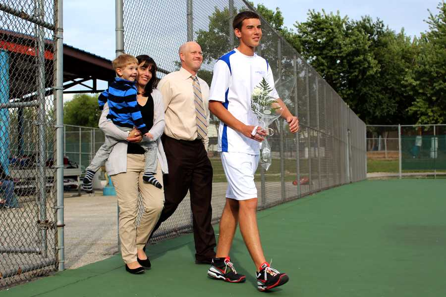 Eric Shrader (12) walks on to the tennis court with his family on Sept. 17 before the match against Laporte. For senior night, the boys received embroidered towels and each gave their mother a bouquet of flowers.