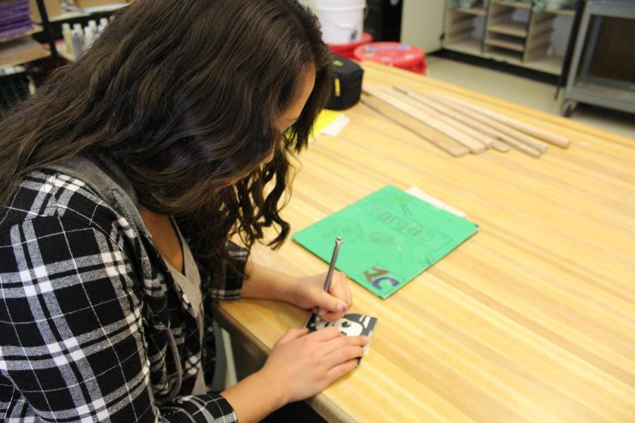 In her Ceramics I class, Jessica Vargas (12) traces her self portrait onto her white tile. The portrait tile will be added onto the new portrait tile yearbook that will be located in the new building.