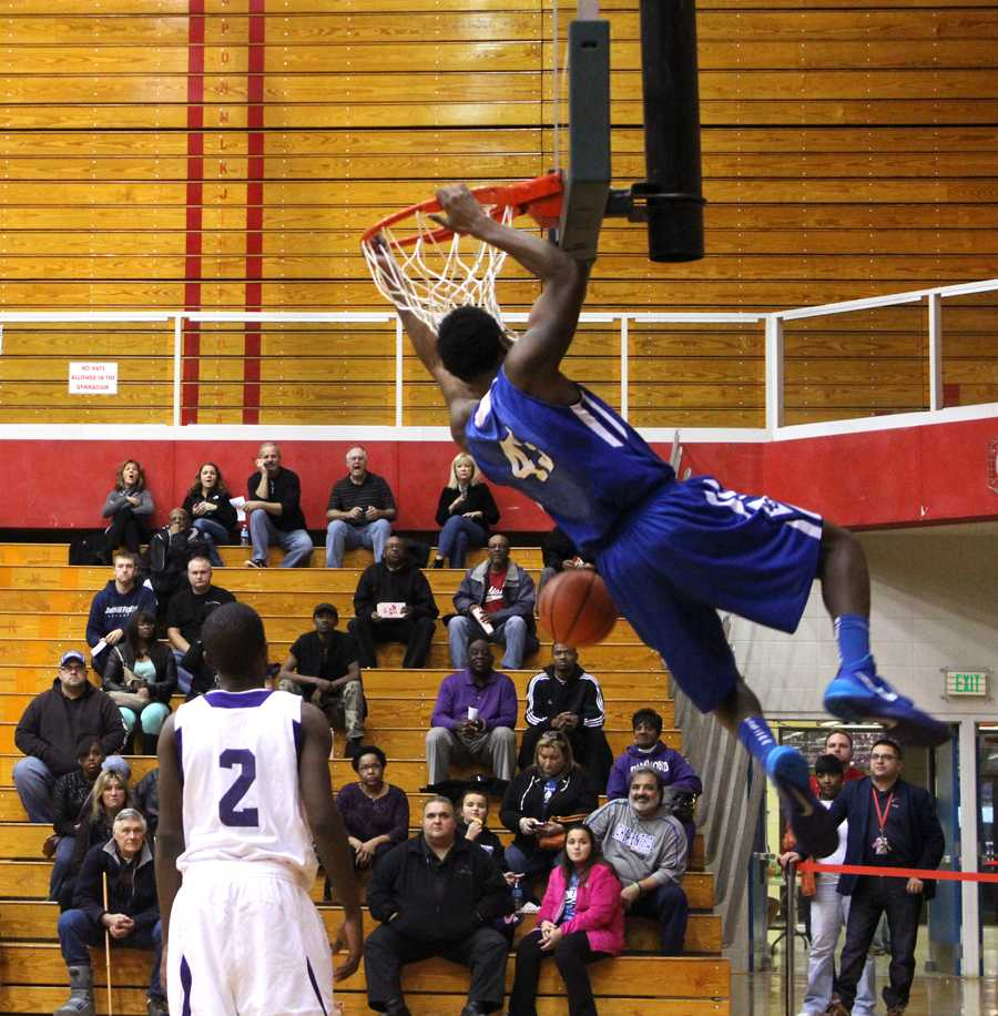 Tyler Wideman (12) slam dunks the ball over many Wildcats' heads. Wideman has signed to play basketball for Butler University next year.