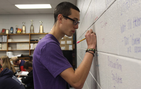 "Theofanis Rauch (12) writes the title of the most current book he read on the back wall of Mrs. Kathryn Clark's classroom.  Rauch sat in the back of the classroom, closest to what has been deemed the ""reading wall."""