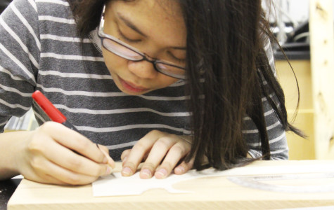 Joyce Cometa (9) finishes up the last meeting project. She cut out a model airplane.
