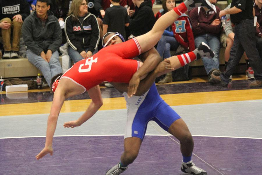 Gelen Robinson (12) lifts Steven Potosky, Crown Point, in the air mid-throw.  Robinson won the State championship in 2013 for the 220 lb weight class.