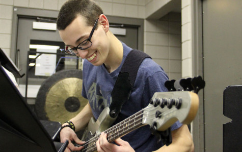 Theofanis Rauch (12) smiles while playing the bass along with the rest of the band. In winter percussion, there is modern rock four-piece (drums, guitar and bass) that plays along with the other instruments.