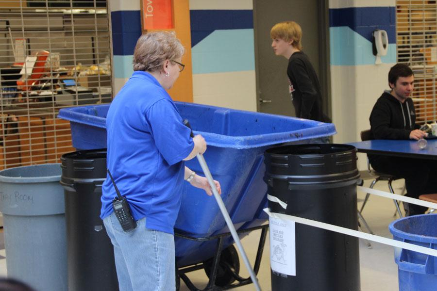 A custodian mops up the floor in the north cafeteria on Feb. 20.  The garbage cans were their collecting water that was coming in through the ceiling.