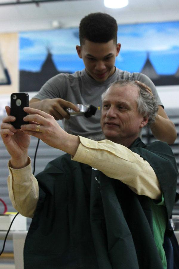 "Mr. Eric Bushong, Math, takes a ""selfie"" as gets his head shaved.  There was 30 participants getting their haircut."