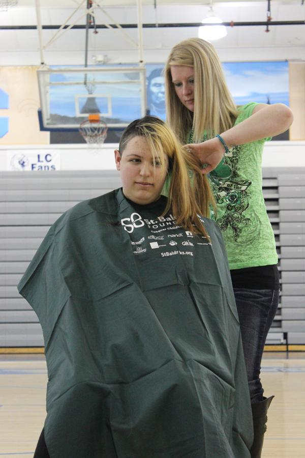 Linda Gonzalez (12) sits patiently as the second half of her head is shaved. Gonzalez, along with Alayna Prisby (11), Nicole Kekelik (12) and Alexis Murphy (11) shaved their entire heads for the cause.
