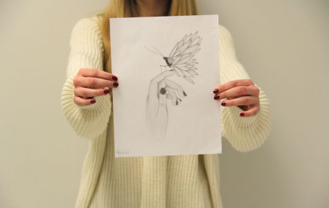 Alexis Curatolo holds up her most recent drawing of a butterfly sitting on a girl's hand.  It took Curatolo about an hour to complete this drawing.