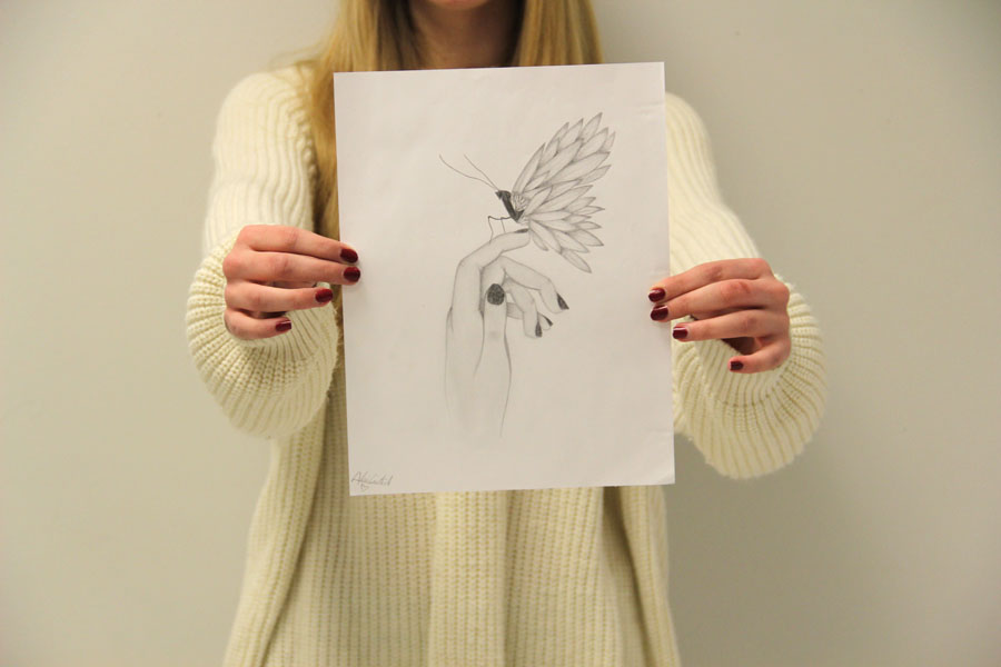 Alexis+Curatolo+holds+up+her+most+recent+drawing+of+a+butterfly+sitting+on+a+girl%E2%80%99s+hand.++It+took+Curatolo+about+an+hour+to+complete+this+drawing.