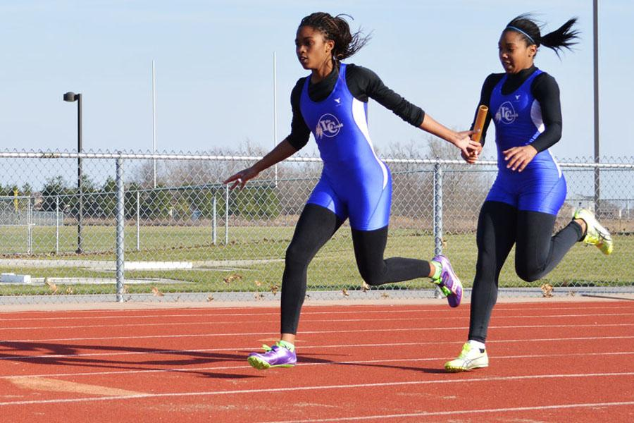 Victoria McKenzie (10) and Parriss Bettis(12) hand off a baton. The girls ran the 4X1 race.