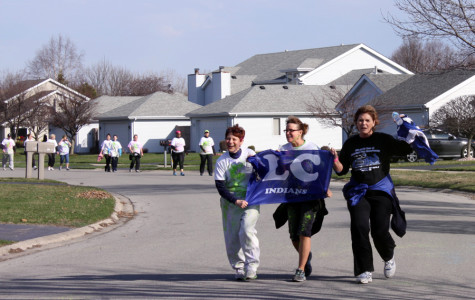Mrs. Louise Tallent, FACS, along with two friends run to the finish line with a Lake Central flag.  They were running the Tri Kappa Tie Dyed Dash, a 5K run/walk on April 12.