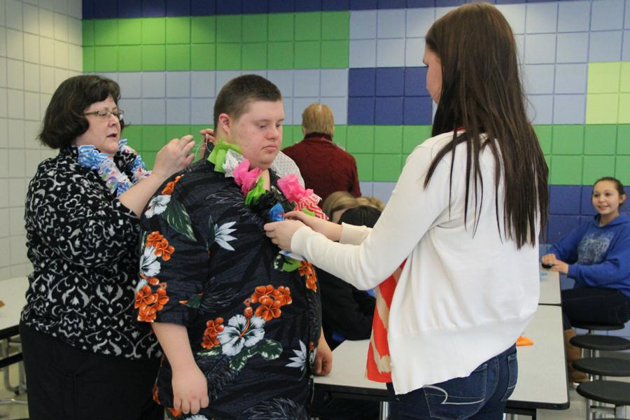 Camryn+Halfeldt+%289%29+and+Mrs.+Kim+Freeman%2C+Physical+Education%2C+help+Jake+Kelley+%2812%29+secure+his+necklace.+This+luau-themed+meeting+took+place+in+the+front+of+the+cafeteria.+