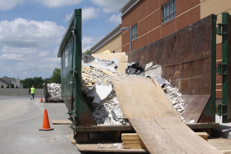 Debris from construction inside of the school is outside and ready to be disposed of. There is lots of debris from the destruction of the wall that once separated the cafeteria and main street
