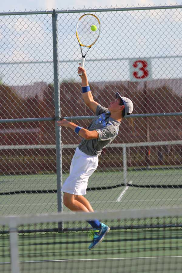 John Mamelson (11) hits a deep forehand lob from the baseline. He finished the Crown Point match with a loss of 6-0, 6-1.