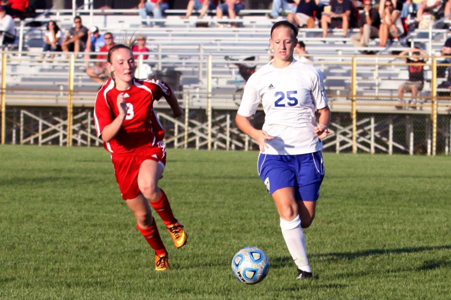 Abby MeseBerg (9) and Kaila Crague (11) run to get the ball. The girls faced off to get the ball.