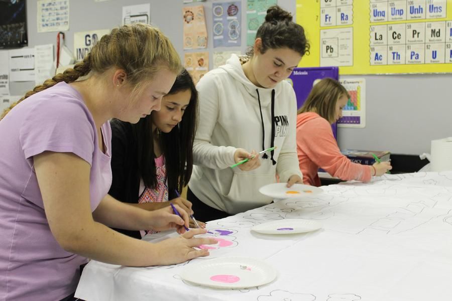 Members of Freshman Class Cabinet meet on Friday, Sept. 19.  Jaclyn Gruver (9), Jazmyn Zapata (9),  Faith Cooper (9) and Ashley Wasserman (9) worked on completing their 1960s themed homecoming banner.  File Name: