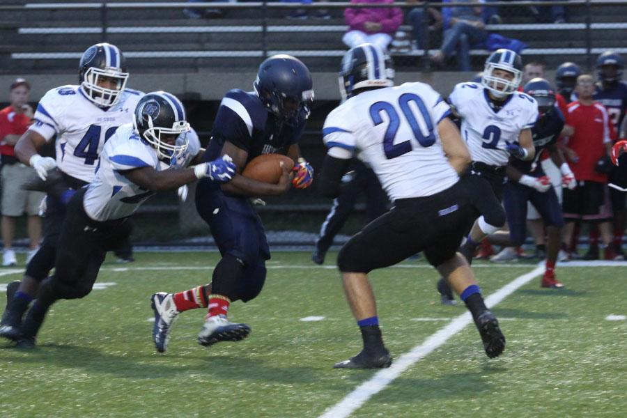 Lucious Pilate (11) tackles an East Chicago player as he runs with the ball.  Pilate was an integral part of the Indian's defensive line.