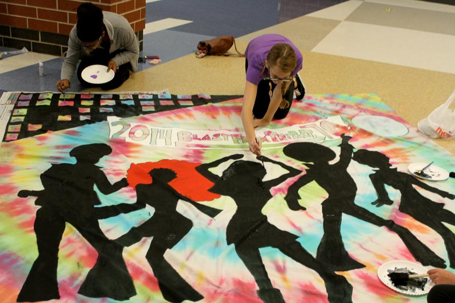 Victoria Wilkes (10) and Nkem O'Gonuwe (10) work on a banner for Homecoming week. The banner was hung along Main Street.
