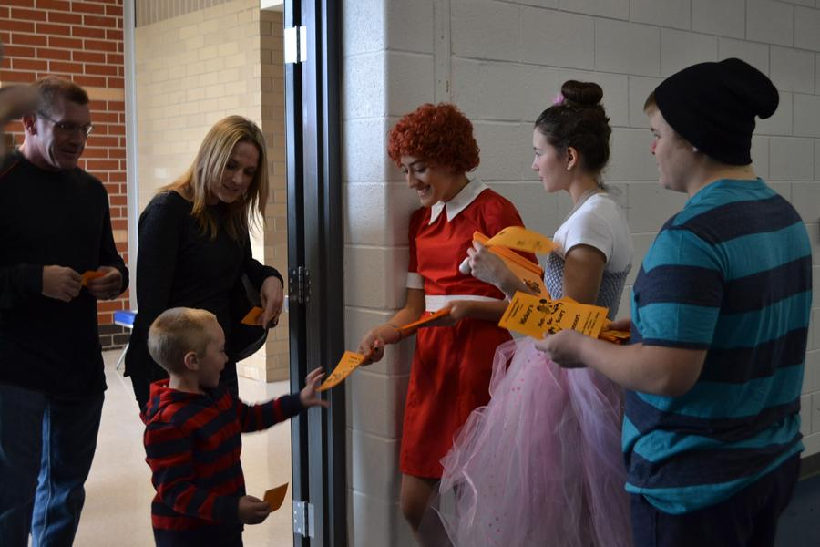Alayna Prisby (12), Stephanie O'Drobinak (10) and Jackson DeLisle (11) greet audience members and distribute concert pamphlets.  Inside the brochure was names of students and what parts they participated in and the layout of the performance.