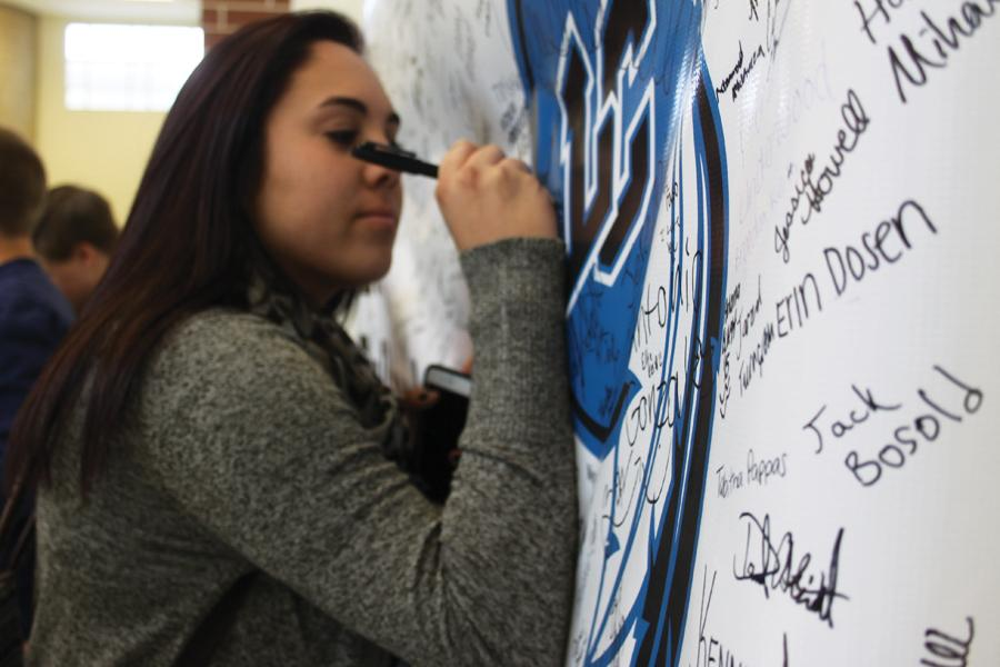 Gabriella Gomez (12) signs her name on the poster during B lunch. Gomez received her wristband directly after signing.